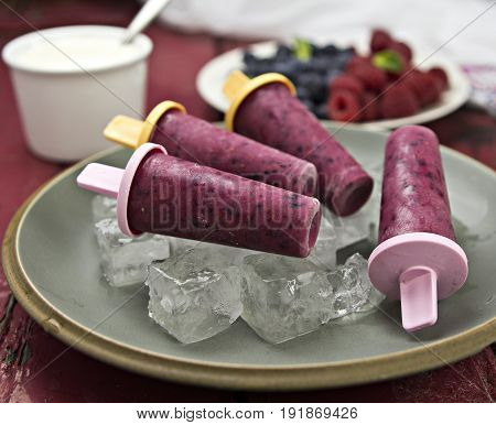 Blueberry and raspberry summer popsicles on blue plate