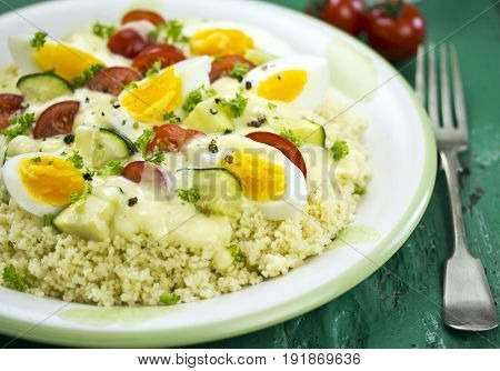 Egg, tomatoes, courgette ragout served on couscous