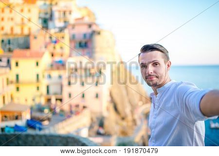 Tourist looking at scenic view of Manarola, Cinque Terre, Liguria, Italy