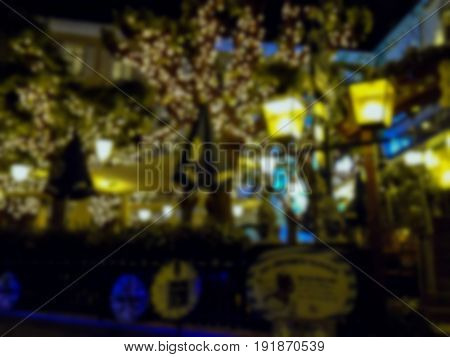 Blured view of Christmas decorated and illuminated trees at street restaurant