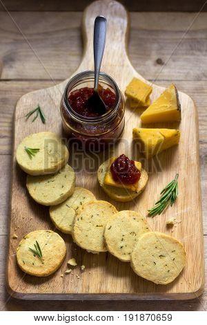 Rosemary crackers on cheese board with relish