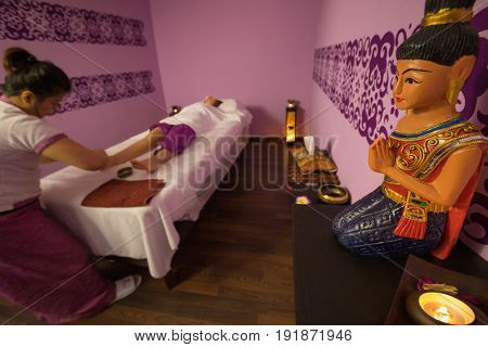 Woman does thai massage for woman on couch in spa room, focus on asian statue