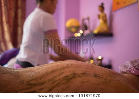 Female back in sand during thai massage, therapist out of focus in spa room