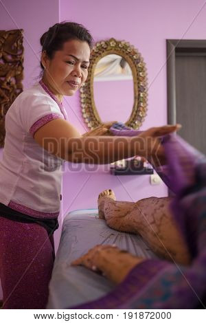 Massage therapist does thai massage of legs with sand and oils for woman on couch in spa room