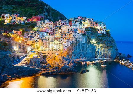 Stunning view of the beautiful and cozy village of Manarola in the Cinque Terre Reserve at sunset.