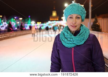 Happy woman stands on ice rink outdoor at night, shallow dof
