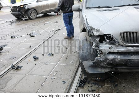 Group car accident with many damages on street, man out of focus at winter