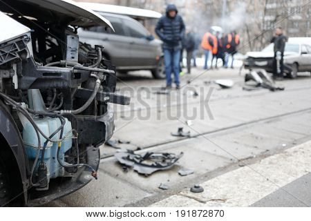 Group car accident with many damages in city, people out of focus at winter