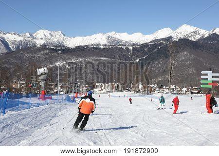 Skiers at ski resort in mountains at winter day in Krasnaya Polyana village, Sochi, Russia