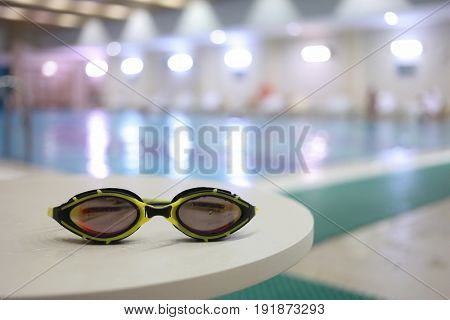 Wet goggles for swimming on table near indoor pool, pool out of focus
