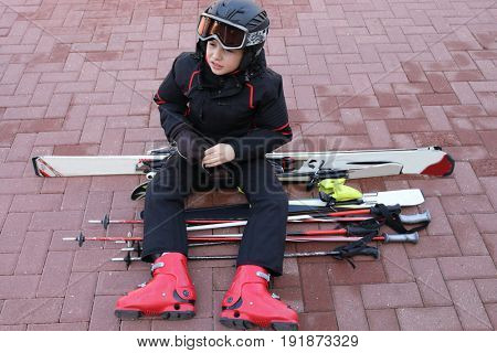 Boy in helmet and ski suit sits on ski on pavement and looks away