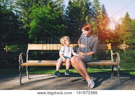 Pregnant woman with child on nature. Mother and son are talking and spending time together outdoors. Child looking at her mother pregnant tummy. Pregnancy new life family parenthood concept