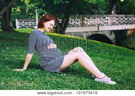 Beautiful pregnant woman in dress on nature outdoors with copy space. Expectant mother holds hands on belly on natural background of green grass in park. Pregnancy expectation new life concepts.