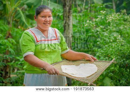 LAGO AGRIO, ECUADOR - NOVEMBER, 17 2016: Woman demonstrates cooking yucca tortillas in an outdoor kitchen in a Siona village in the Cuyabeno Wildlife Reserve, Ecuador.