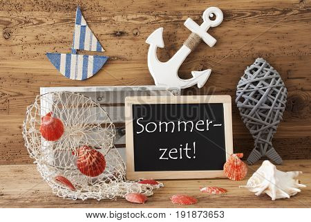 Blackboard With Nautical Summer Decoration And Wooden Background. German Text Sommerzeit Means Summertime. Fish, Anchor, Shells And Fishnet For Maritime Contex.