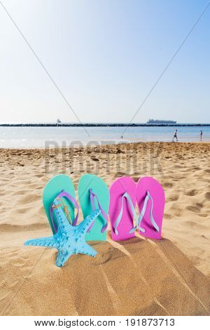 Summer beach fun - summer colorful blue and pink sandals with starfish in beach sand