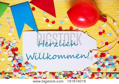 White Label With German Text Herzlich Willkommen Means Welcome. Close Up Of Party Decoration Like Streamer, Confetti And Balloon. Flat Lay Or Top View. Yellow Wooden Background