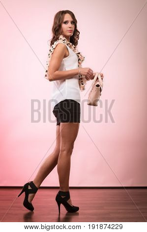 Elegant outfit. Female fashion. Girl in full length fashionable clothes high heels holding bag handbag.