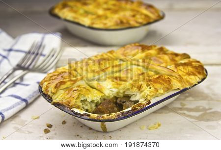 Beef and guinness puff pastry pies in enamel ovenproof dish