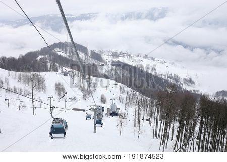 Cableway at winter day in ski resort in mountains in Krasnaya Polyana village, Sochi, Russia