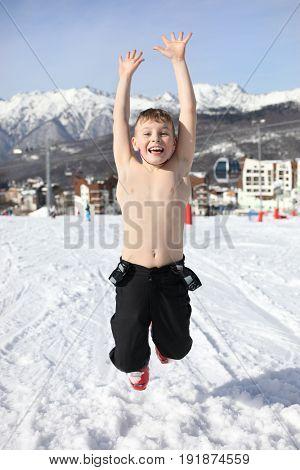 Happy half-naked boy jumps at ski resort at winter day among mountains