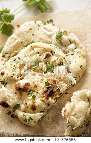 Fresh coriander naan bread on wooden board