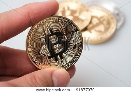 Hand holding golden bitcoin isolated on white background