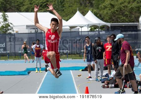 A male high school athlete triple jumps during the CHSAA Catholic State Championships in New York on Saturday 5/27/2017