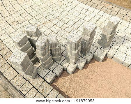 Closeup of unfinished pavement path with set of concrete pavement blocks