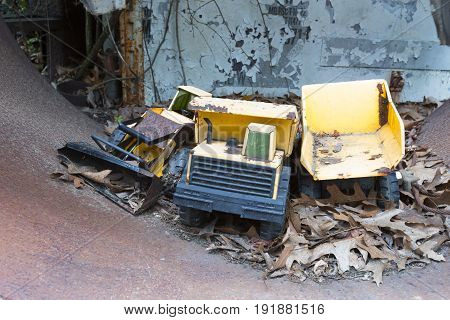 Toy heavy equipment in leaves inside rusting pipe in junkyard.
