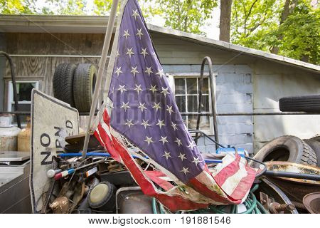Shredded and tattered American flag on pile of rubbish in junkyard.