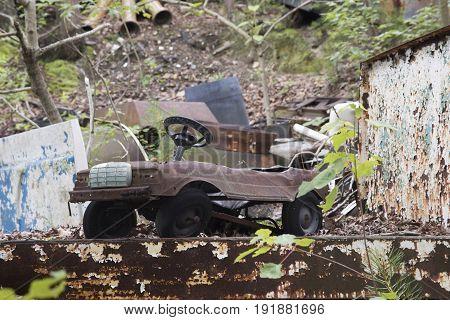 Rusting toy model car in wooden junkyard.