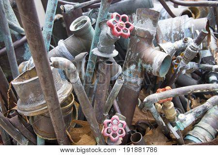 Plumbing metal pipes and faucets in junkyard.