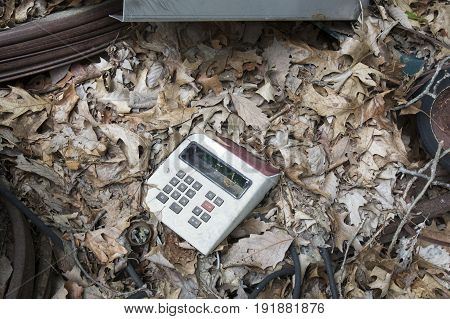 Old obsolete calculator in dry leaves among rusting scrap metal in junkyard.