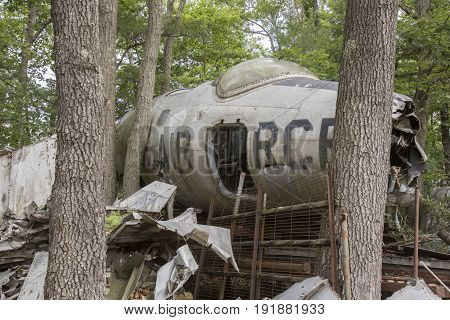 Nose cone of wrecked US Air Force fighter jet in trees of junkyard.