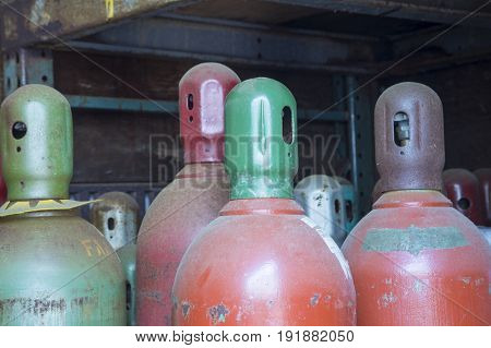 Industrial gas cylinders in storage shed of junkyard.