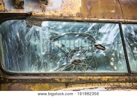 Abstract patterns in broken window of rusty old school bus.