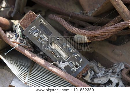 Automotive stereo cassette player and radio on salvage pile in junkyard.