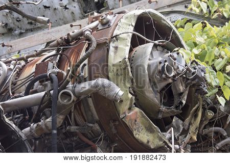 Rusting airplane engine from wreckage among weeds in junkyard.