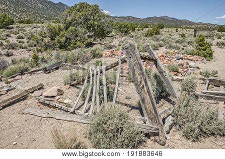 Part of an old cemetery in Utah with various methods of marking burial plots. Someone has visited each grave recently and left something for the dead.