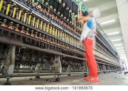 female worker standing beside thread making machine inside cotton millindustry concepts.