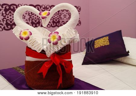 Lounge for thai massage with towels in form of swans in empty pink room