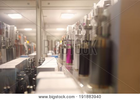 Many Electronic cigarettes are on shelves in shop, shallow dof