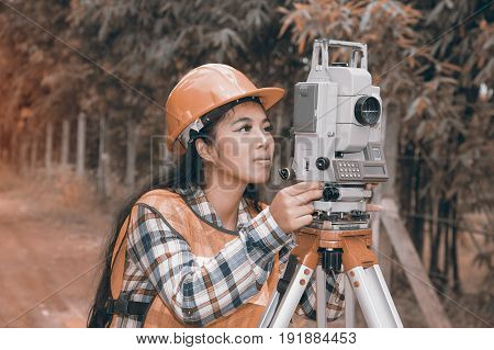 Female Surveyor or Engineer making measure by Theodolite on the street in a field.