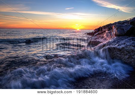Beautiful Sunrise Beach Background. Waves crash onto the rocks of a Lake Huron beach with a sunrise horizon in the background. Lexington, Michigan.