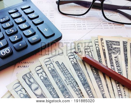 Business, finance, savings, banking or  loan concept : Pencil, calculator, eyeglasses, money and savings account passbook or financial statement on white background