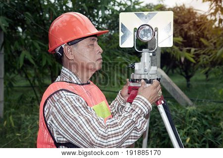 Surveyor or Engineer making measure by prism reflctor on the street in a field.