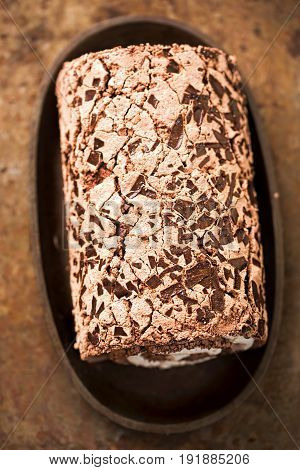 Chocolate meringue roulade on brown table background