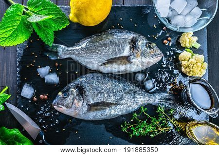 Fresh fish dorado top view. Spicy herb and vegetables. Spice on black stone board. Healthy food cooking.