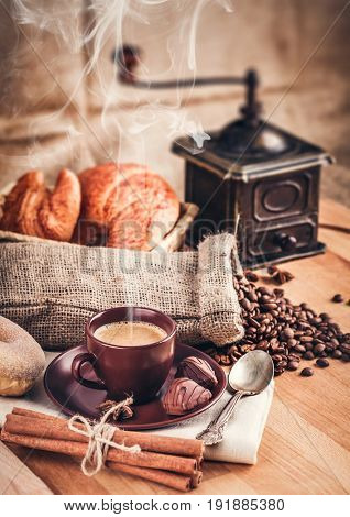 Cup fragrant hot coffee with bean chocolate sweet and croissant in vintage rustic style cinnamon steam smoke on wooden board for bracing morning breakfast.